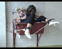 Bound in a straitjacket which is attached to a bed with rope