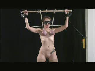 Audrey is chained, facing the wall her hands encased in mediaeval iron balls