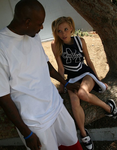 Miniature cheerleader is seated on a giant black dick