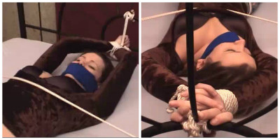 A  ball gag is pulled tightly in her mouth and ropes