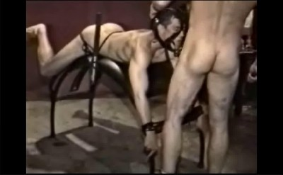 Roped over the arch Chris begs for dick as his ass is strapped hard and fucked with a huge dildo