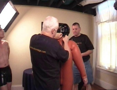 SI – Zoie in a blow up orange heavy rubber catsuit