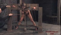 Shes bent over with her head, wrists, and ankles locked in stocks