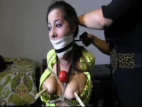 A woman appears and adds more rope to her body, eventually removing the ballgag