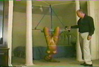 She remains bound here and the captor even tied her legs together as well