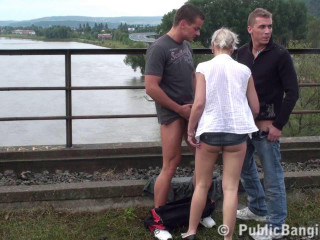 Blonde and two guys on the bridge at the river