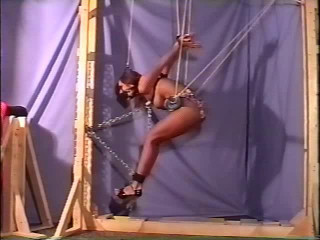 She's roped to the ceiling while in swimsuit and while her mouth is frosted with cloth