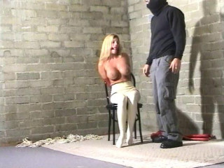 She looks vulnerable while seated on the floor with her assets bound with cord