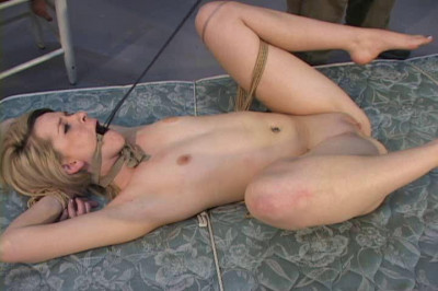 The ropes connecting her wrists to her ankles allow her limited movement
