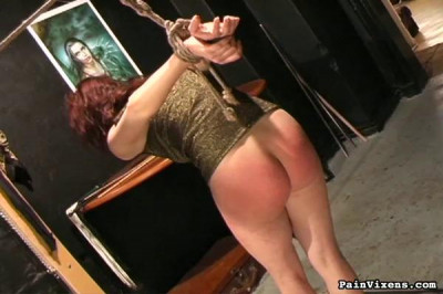 Her bra has been stripped off and her rope gag pulls her head back