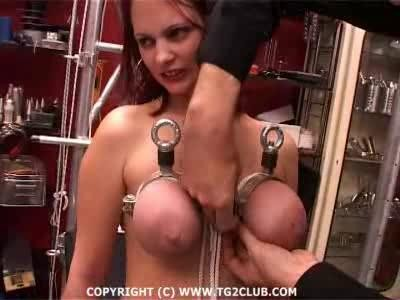 Hanging on winch by he hooks that stab through breasts and nipples