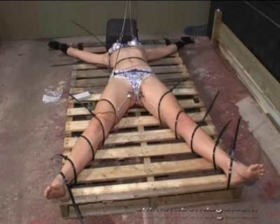 Ariel Is Sat Upright On A Wooden Pallet And Ties Lengths Of String (2013)