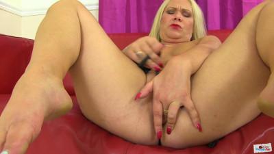 Horny blonde milf masturbates in the red sofa