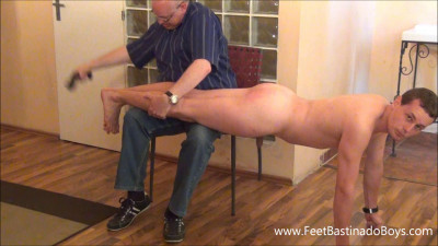 The master, continues to punish tom with a leather belting on the bare feet, in the wheelbarrow posit