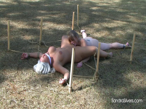 Buxom Nude MILFs Staked out, Spread-Eagle Outdoors for Oral Sex & Struggles!