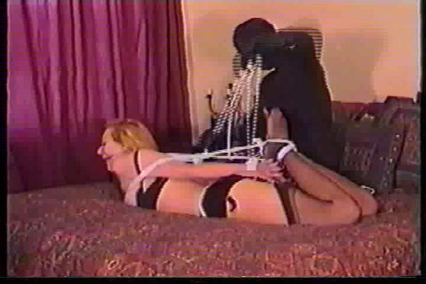 This lady is bound in rope while seated on a chair