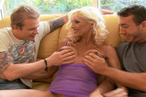 Busty Blonde MILF Takes On 2 Young Cocks