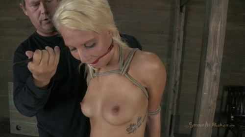 Blond head has her hands tied up with ropes behind the back