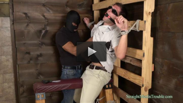 The masked man has a sexy young guy tied to the rack